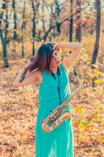 Woman with saxophone standing in forest during autumn