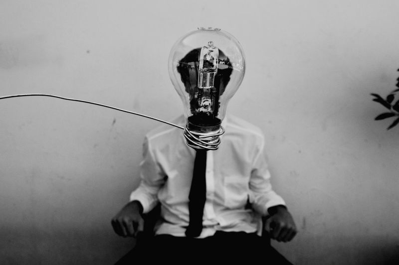 Close-up of electric bulb against man sitting on chair