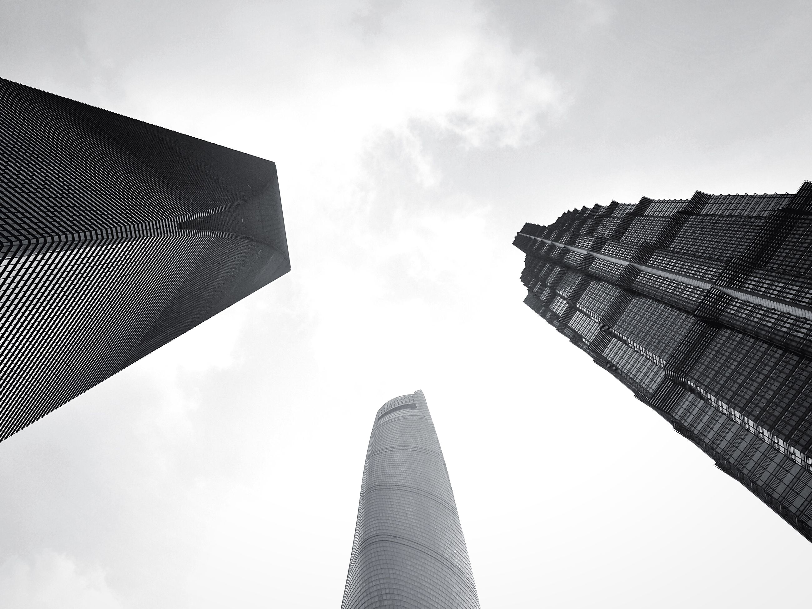low angle view, architecture, building exterior, built structure, skyscraper, tall - high, modern, tower, office building, city, sky, tall, building, directly below, cloud - sky, day, outdoors, glass - material, no people, architectural feature