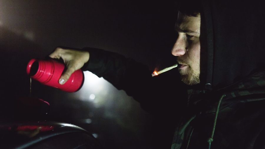 Close-up of man pouring drink in container while smoking at night outdoors