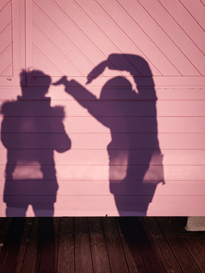 Silhouette shadow of a girl dancing on a pink wooden background.