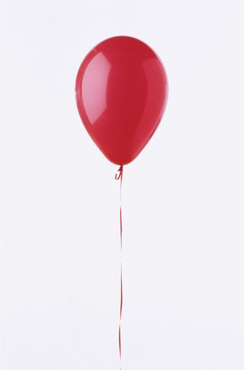 Low angle view of red balloons against white background