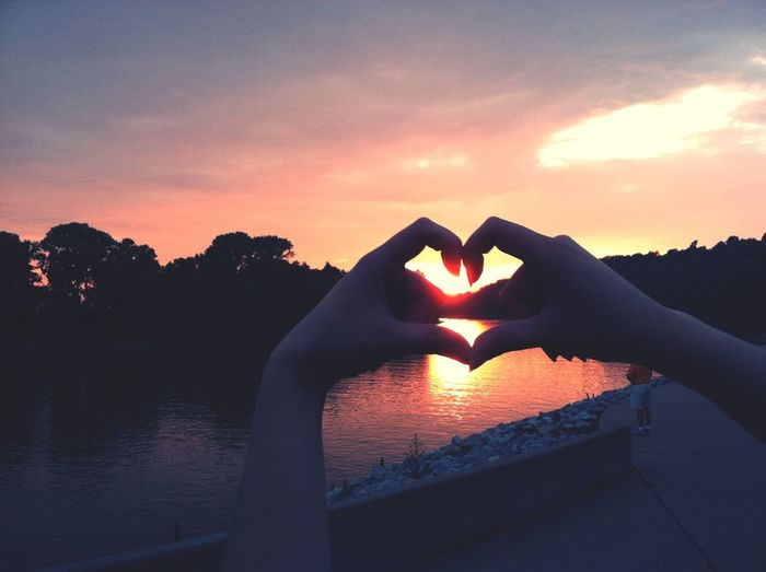 Woman's hands in shape of heart against river at sunset