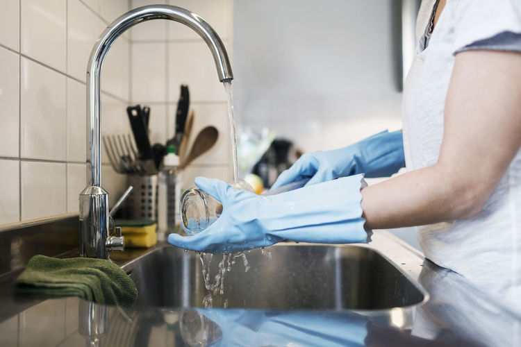 Midsection of man with faucet in kitchen at home