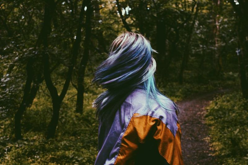 Woman Tossing Dyed Hair In Forest