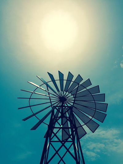 Low angle view of water pump windmill against sky