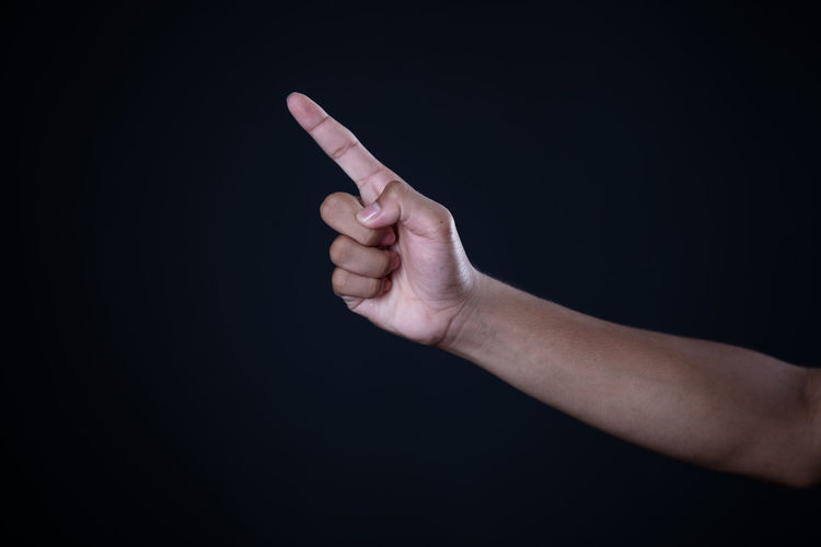 Midsection of person hand holding paper against black background