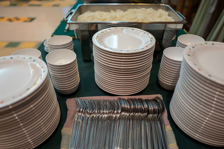 Close-up of stacked plates and cutlery on table
