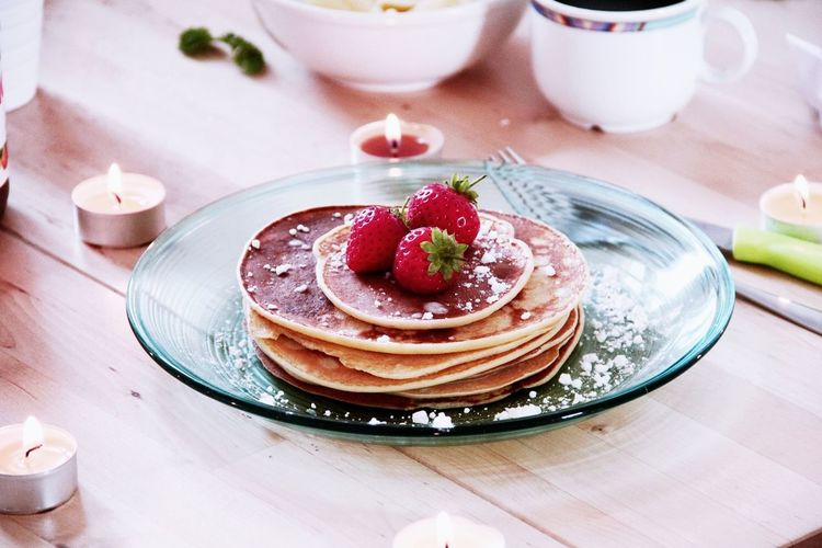 Strawberries On Pancakes In Plate Over Table