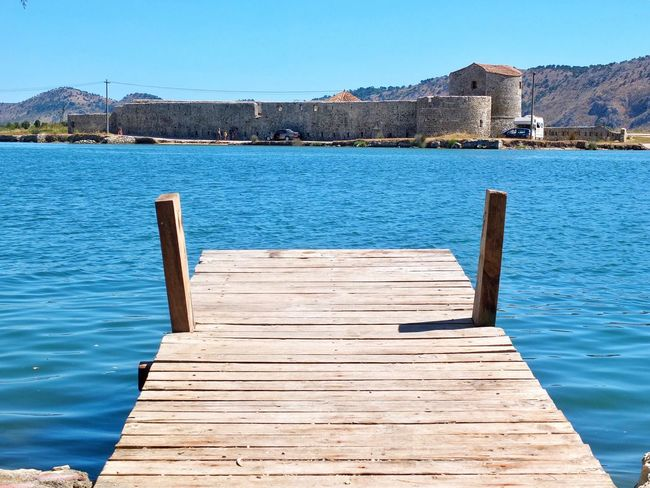 Wood - Material Pier Water Built Structure Day Outdoors Architecture Tranquility Jetty Clear Sky Tranquil Scene Blue Building Exterior No People Nature Mountain Lake Scenics Wood Paneling Beauty In Nature Albania Butrint Castle