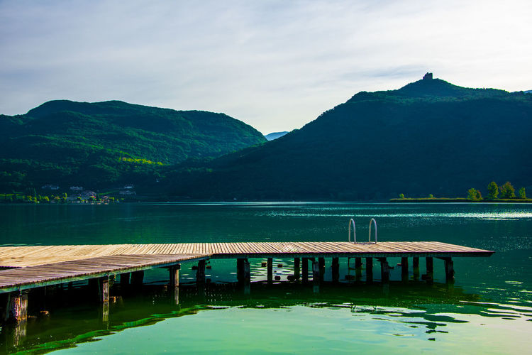 Small wooden jetty among the reeds of lake caldaro in bolzano, italy