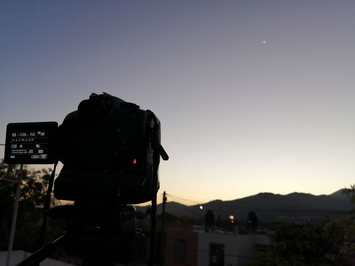 Silhouette of camera against clear sky during sunset