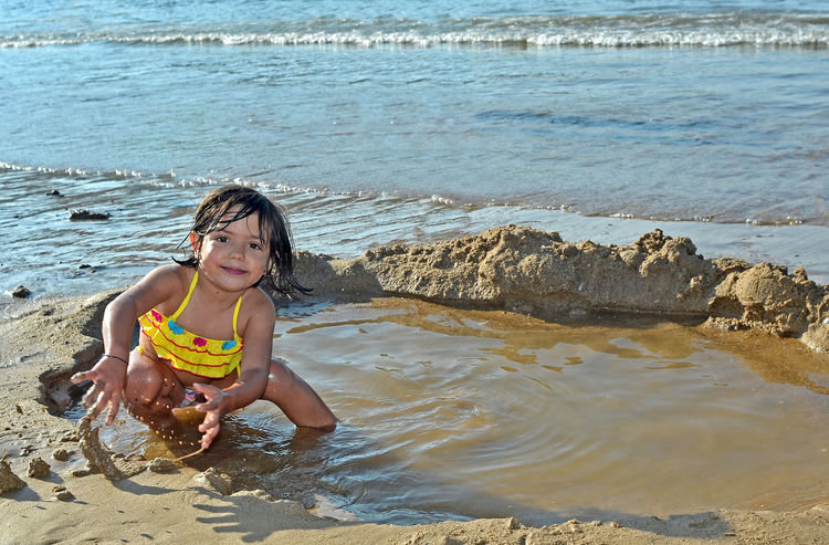 Baby girl playing with water and sand on the beach