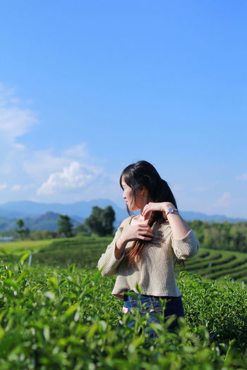 Contemplating woman adjusting hair while standing amidst tea plantation field against sky