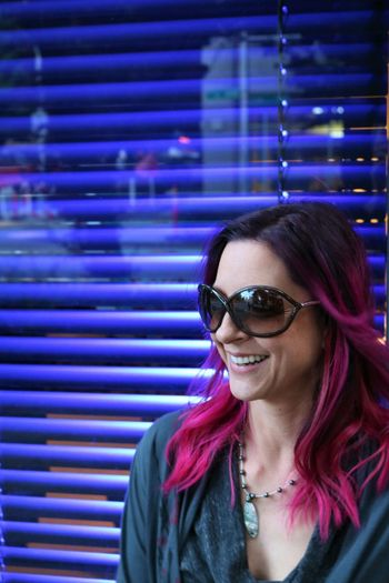 Smiling Young Woman With Dyed Pink Hair Against Blue Blinds