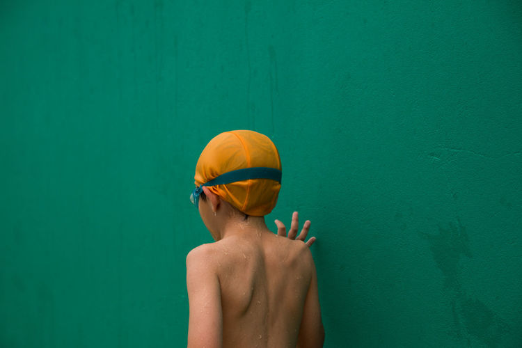 Rear View Of Wet Shirtless Boy Standing Against Green Wall