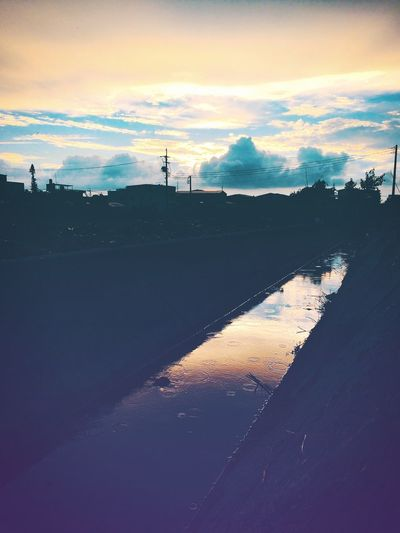 Scenic view of silhouette canal against sky during sunset