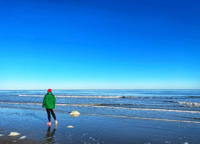 Rear view of man on beach against clear blue sky