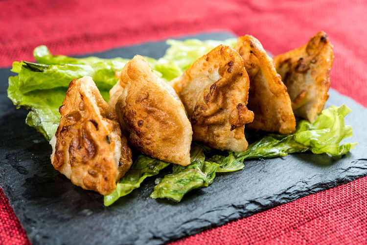 High angle view of deep fried chicken wings with lettuce served on slate