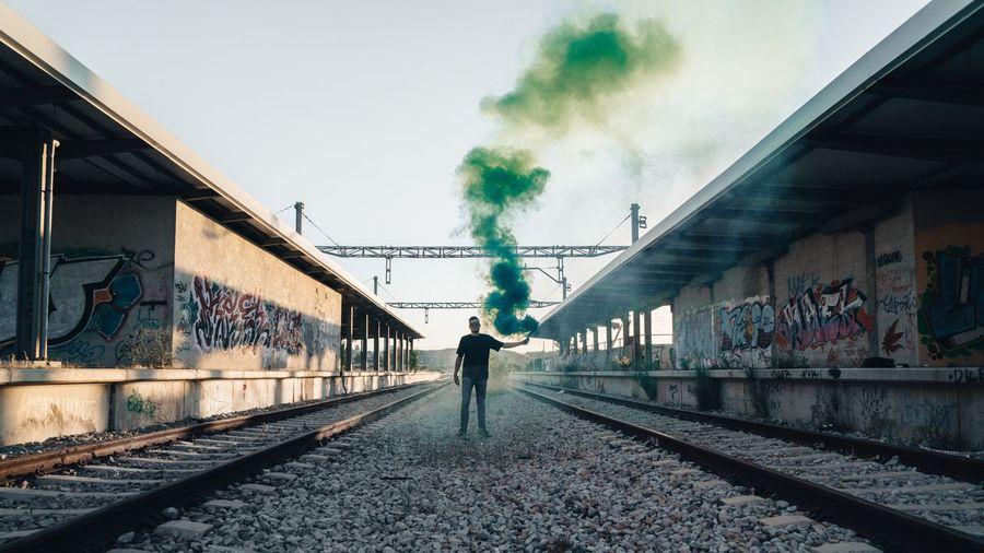 Young man holding smoke bomb while standing on railroad tracks against sky