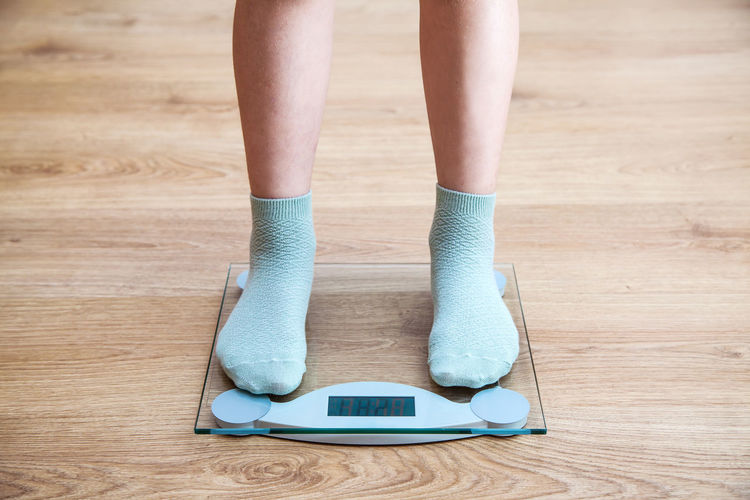 Low section of woman wearing socks while standing on weighing scale