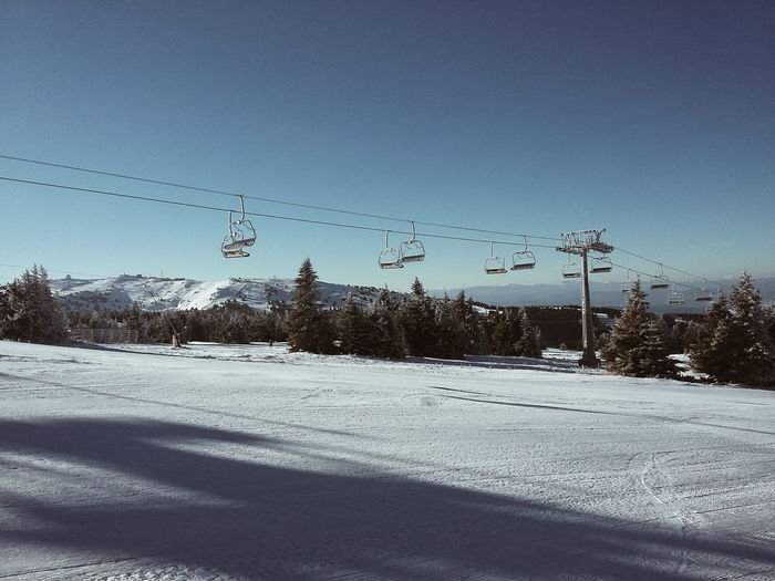 Low Angle View Of Overhead Cable Car Over Snowy Hill Against Clear Sky