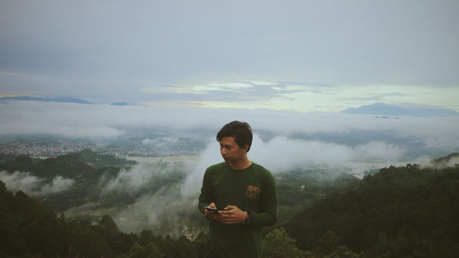 Young man holding mobile phone while standing on mountain
