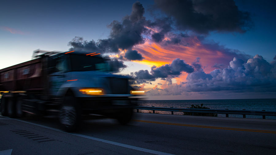 Cars on road by sea against sky during sunset