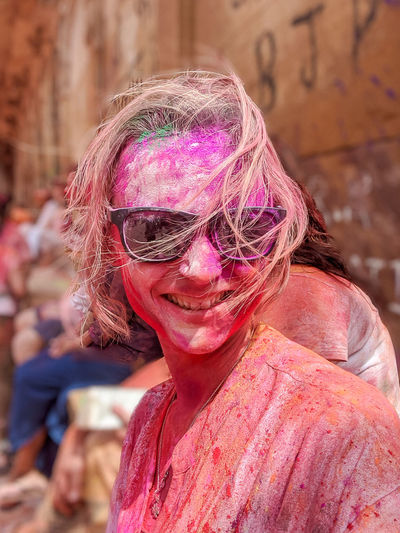 Portrait of woman celebrating holi with pink and red powder paint