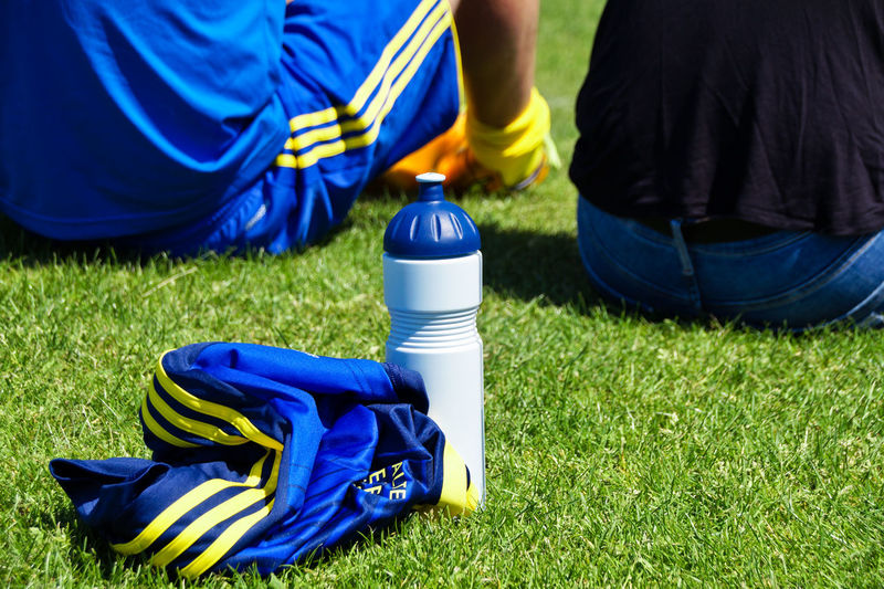 Low Section Of Soccer Player Sitting By Water Bottle On Field