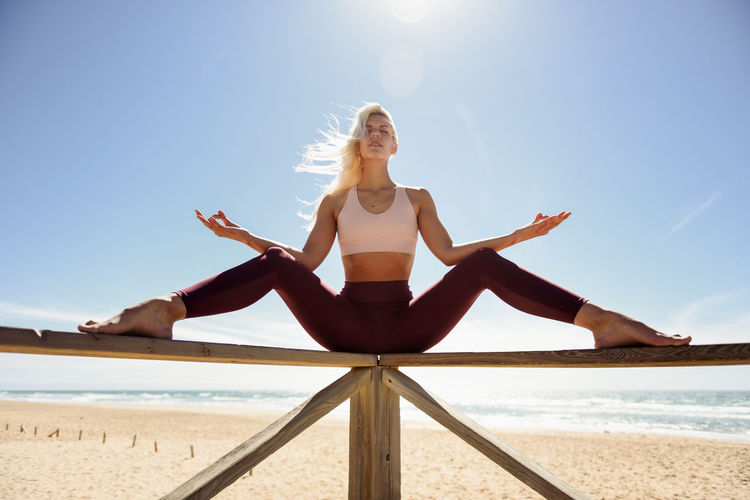 Low angle view of woman doing yoga on railing at beach