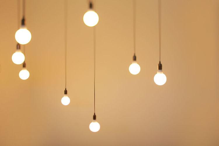 Illuminated light bulbs against beige background