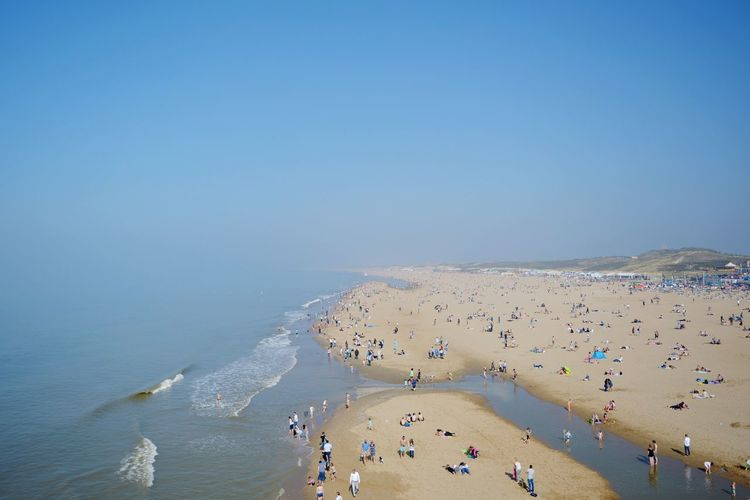 Panoramic View Of People On Beach Against Clear Blue Sky