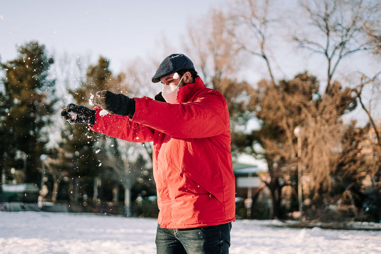 Man playing while standing in snow