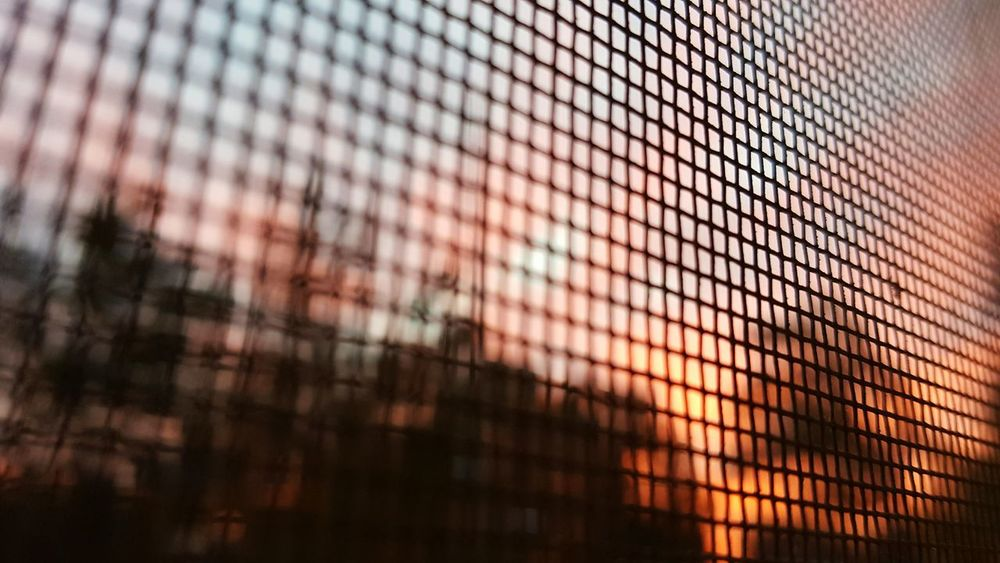 Sunrise Horizon Looking Through Pattern Window Screen Seamless Pattern Backgrounds Close-up Full Frame Sky Sun Sunset Red Sky Pink Sky Outdoors Looking Out Abstract Blurred