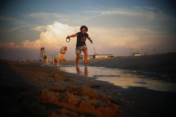 Woman with dogs running on shore at beach against sky during sunset