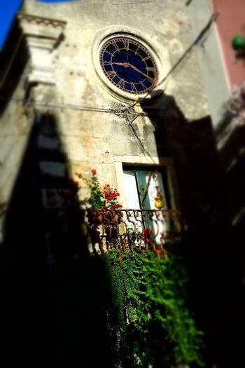 Selective Focus Blurry On Purpose Shadows & Lights Balcony Clock