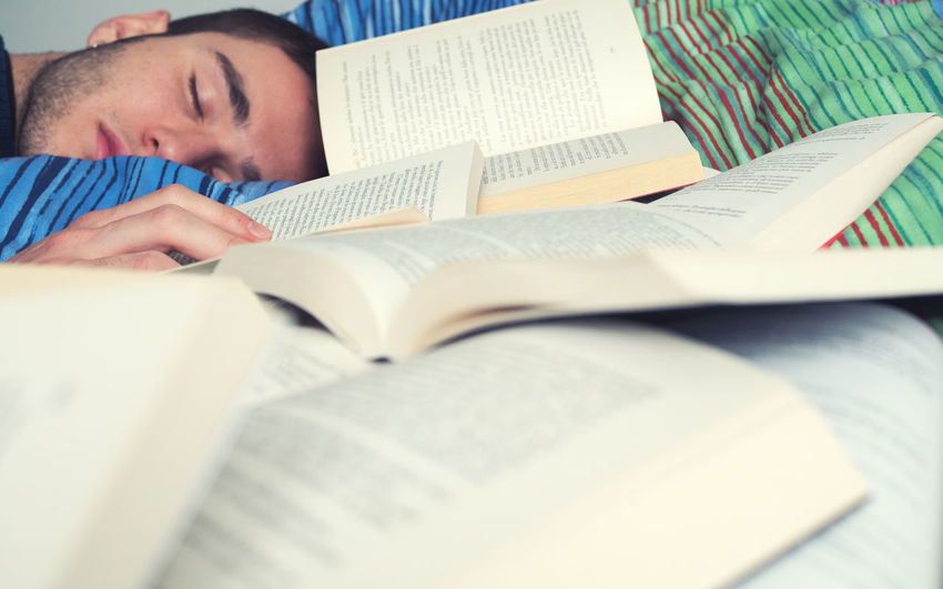 Close-up of man sleeping next to open books