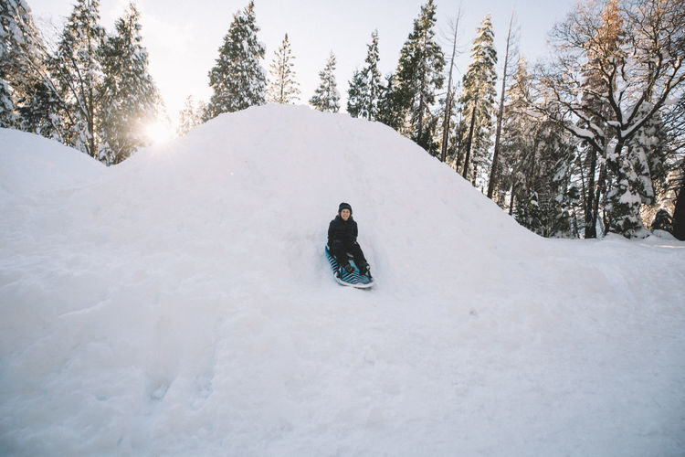 Rear view of person on snow covered land