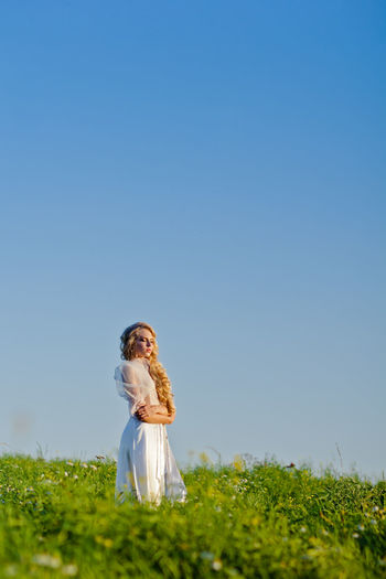 Young Woman Standing On Field Against Clear Blue Sky