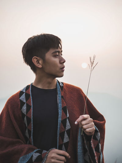 Young man looking away while standing against sky during sunset