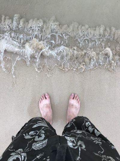 Low section of man standing at beach