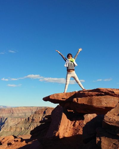 Woman standing on rock by canyon