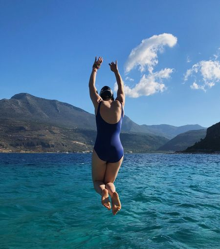 Rear View Of Woman Jumping In Sea Against Blue Sky