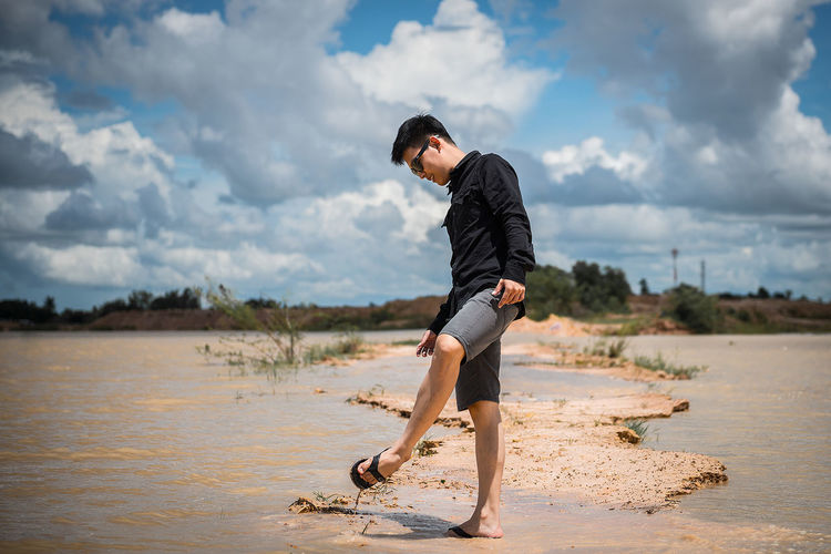 Water Sky One Person Full Length Beach Lifestyles Real People Young Adult Land Leisure Activity Young Men Beauty In Nature Cloud - Sky Nature Casual Clothing Sea Day Side View Outdoors