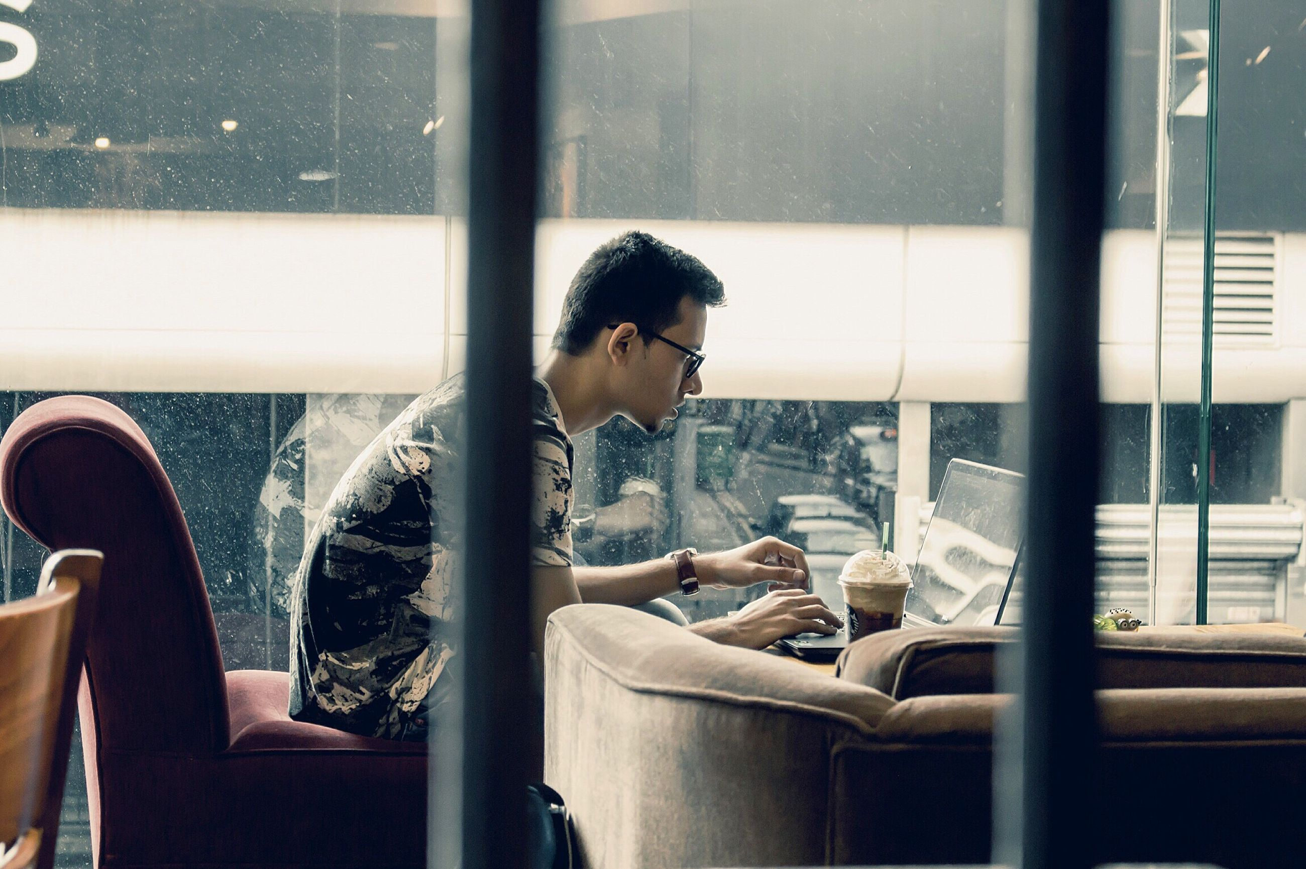 real people, window, sitting, one person, coffee - drink, indoors, coffee cup, eyeglasses, drink, table, side view, cafe, casual clothing, chair, lifestyles, young adult, holding, wireless technology, day, young women, technology