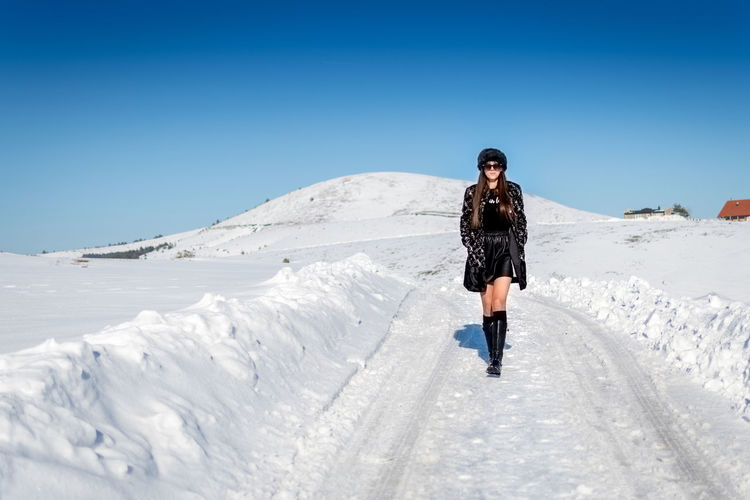 One Person Snow Winter Cold Temperature Young Adult Front View Full Length Lifestyles Leisure Activity Sky Nature Real People Clear Sky Blue Sunlight Day Beauty In Nature Standing Warm Clothing Outdoors Extreme Weather