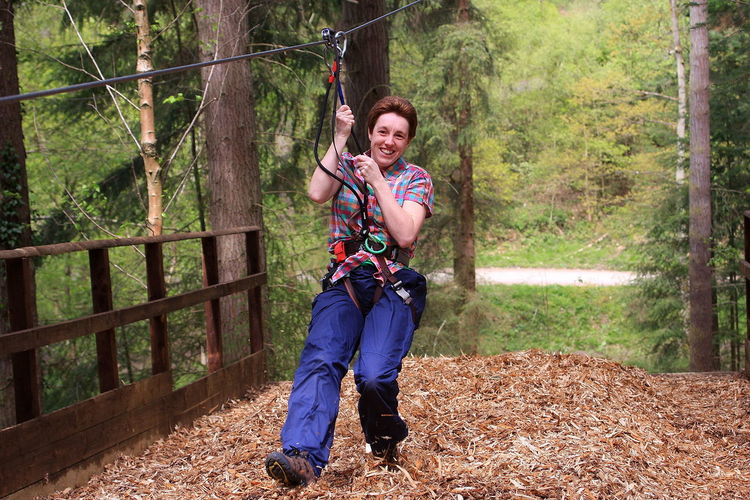 Smiling Woman Zip Lining At Forest