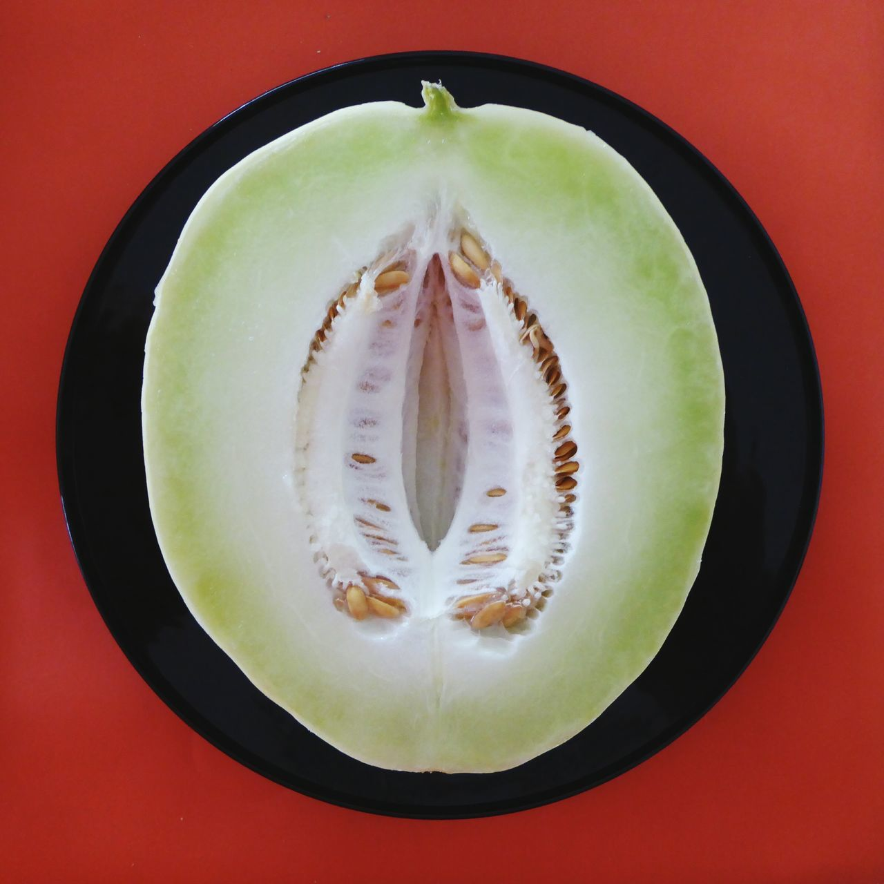 Directly Above Shot Of Halved Honeydew Melon In Plate