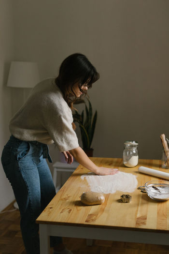 Side view of woman preparing food on table at home
